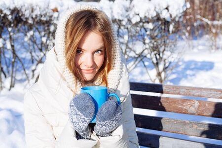 sch�ne frauen: Sch�ne gl�cklich l�chelnde Winter-Frau mit blauen Becher im Freien Lizenzfreie Bilder