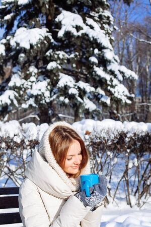 hot chocolate drink: Beautiful Happy Smiling Winter Woman with Blue Mug Outdoor