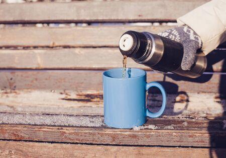 enero: Mujer verter una bebida caliente en la taza del termo en un parque de invierno Foto de archivo