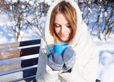 hot cold: Beautiful Happy Smiling Winter Woman with Blue Mug Outdoor