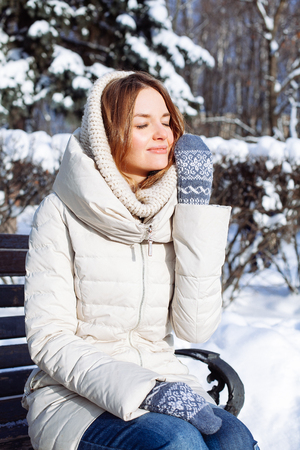 Beautiful winter portrait of young woman in the winter snowy scenery photo