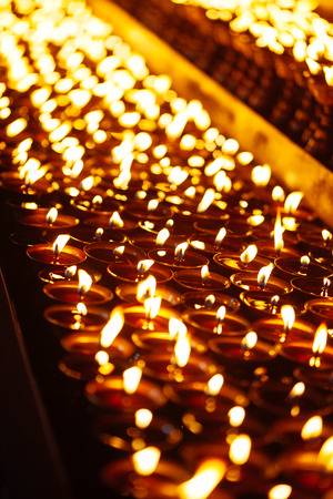 Many candle flames glowing in the dark with shallow depth of field