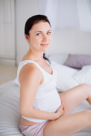 Young pregnant woman is sitting in the bedroom in white
