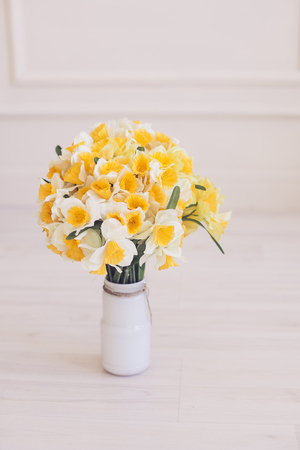Narcissus flowers bouquet in a vase on natural wooden background. Mothers day. Stock Photo