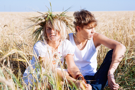 Image of young man and woman on wheat field. Summer day Imagens