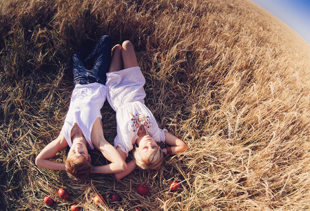 Image of young man and woman lying  on wheat field. Top view, summer day photo
