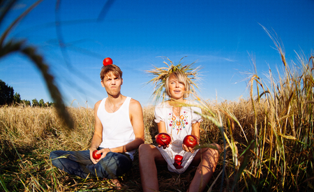 Image of young man and woman with apples on wheat field. Summer day
