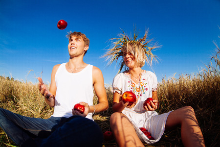 Image of young man and woman with apples on wheat field. Summer day photo