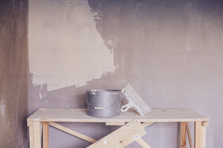 home decorating: Set of plaster trowel tool, spatula and bucket. Construction tools in empty room