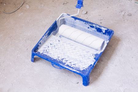 redecorate: Blue bucket with white paint and a brush roller paint tray Stock Photo