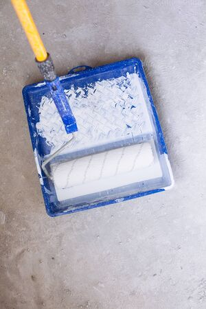 home decorating: Blue bucket with white paint and a brush roller paint tray Stock Photo