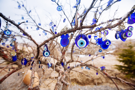 Nazar, charms to ward off the evil eye , on the branches of a tree in Cappadocia, Turkey Foto de archivo