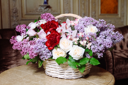 Bouquet of lilacs and red peonies on marble table in interior of the Baroque style