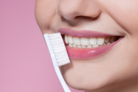 Beautiful young woman smiling with toothbrush  on pink background Imagens