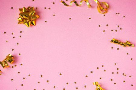 Golden decorations and sparkles on light pink background
