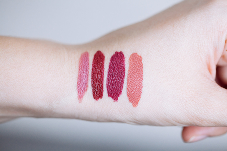 Female arm with lipstick tone color and testing different lipsticks, showing swatches