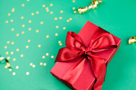 Red gift box and Golden decorations and sparkles on bright  green background