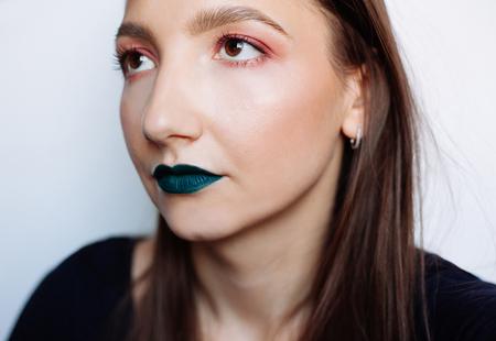 Close-up selfie portret van mooie jonge brunette met creatieve make-up: groene ilpstick en rode oogschaduw Stockfoto