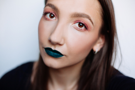 Close up selfie portrait of pretty young brunette with creative make up: green ilpstick and red eyeshadows