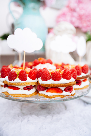 Buffet with sweets. Cakes with raspberries. Sweet table for banquets, weddings, parties. Candy bar.
