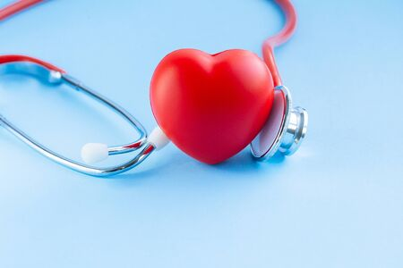 Stethoscope and red heart on blue background. Cardiology and Healthcare concept