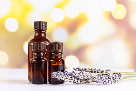 Bottles with organic essential aroma oil with lavender flower on blurred background