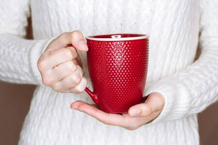 Young woman in white  sweater is holding red cup of tea or coffee. Trying to warm hands with hot drink