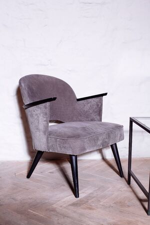Gray anthracite color armchair. Modern designer armchair in the room background. Textile armchair and chair.