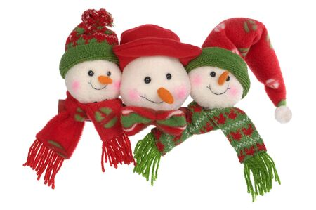 Three toy snowballs in caps and scarfs on a white background