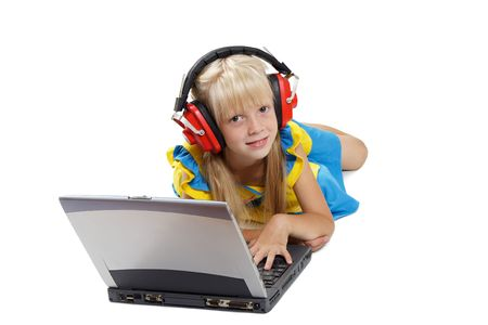 The girl with headphones lays before a portable computer on a white background photo