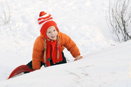 The cheerful girl creeps on a snow on a hill Stock Photo