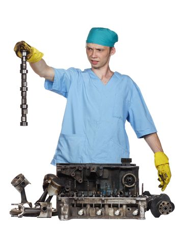 The person holds a detail of the engine in a hand,details of the engine on a white background