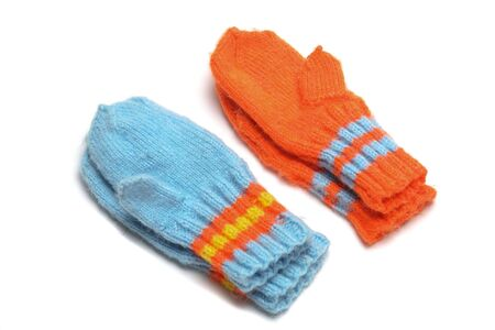2 pairs childrens knitted mittens on a white background