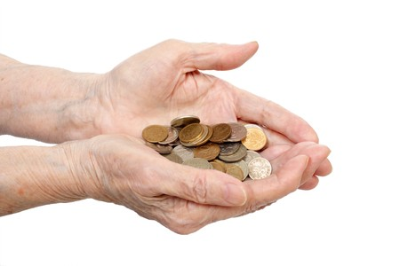 Coins in senile hands are isolated on a white background