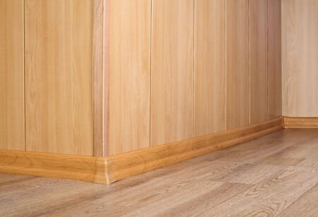 Part of a wooden wall and floor with a parquet photo