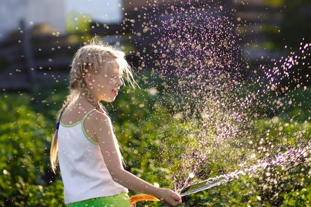 The girl watering from a hose a kitchen garden
