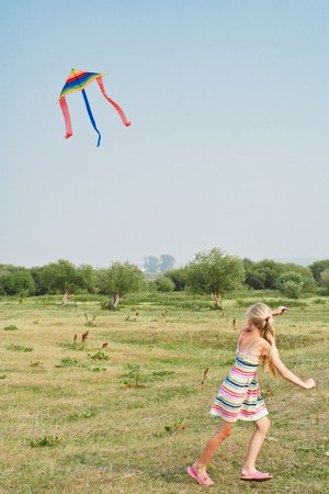 The girl runs on a meadow with a kite