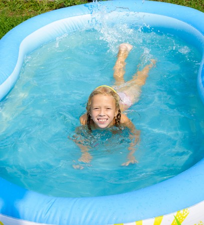 A smiling girl bathes in pool and sprays water