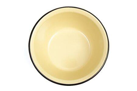 The yellow enameled plate is isolated on a white background Stock Photo