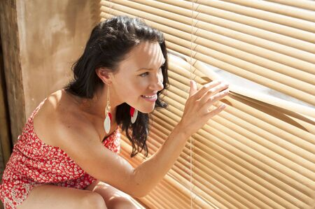 Young brunette looking out the window through the blinds  photo