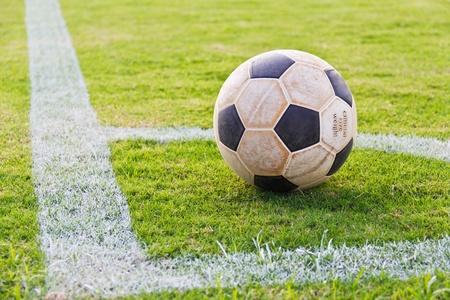 Oude voetbal op de hoek van echt gras voetbalveld, klaar voor het spelen van