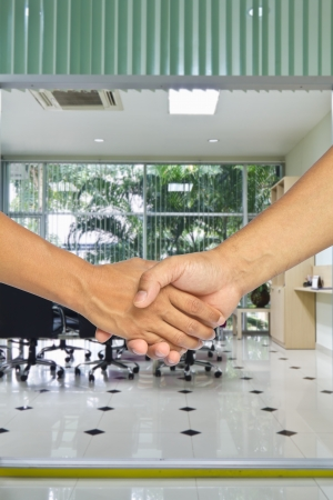 Business handshake with meeting room background, greeting or agreement concept Stock Photo