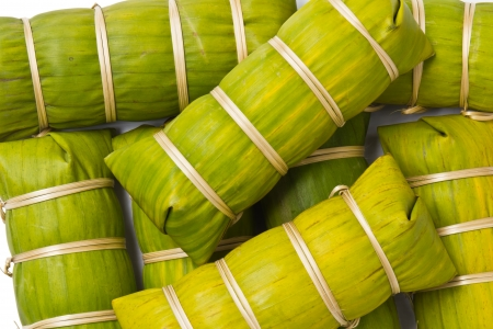 Thai style banana leaf wrapped food, made from sticky rice, pork and peanut photo
