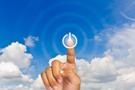 A hand press on illuminated switch-on button on touchscreen, blue sky background Stock Photo