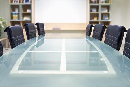 Salle de réunion avec une table en verre haut et fauteuils et tableau blanc