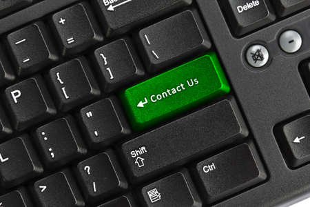 Close up of black pc keyboard, focus on green contact us key, internet concept photo