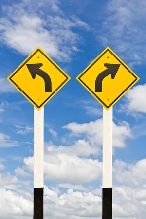 Left and right curved road signpost on cloudy sky background photo
