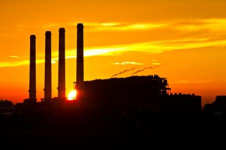 Silhouette de turbine à gaz d'une centrale électrique contre le coucher du soleil