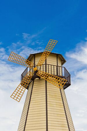 Windmill with yellow vane in blue sky background Stock Photo - 13701111