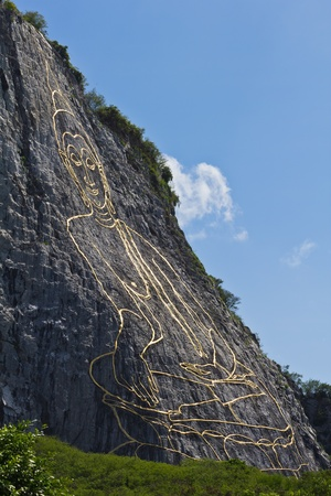 chonburi: Side view of carved buddha image on the cliff at Khao Chee Jan, Pattaya, a travel destination in Thailand